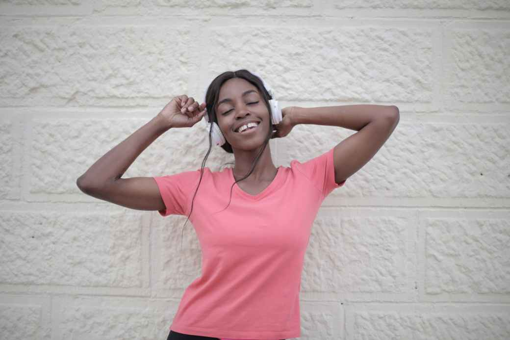 cheerful black woman with earphones dancing